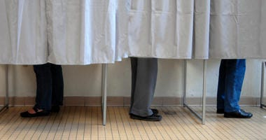 People stand inside voting booths