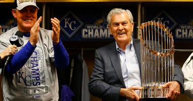 Nov 1, 2015; New York City, NY, USA; Kansas City Royals catcher Salvador Perez (right) and owner David Glass celebrate with the Commissioners Trophy after defeating the New York Mets in game five of the World Series at Citi Field. The Royals won the World