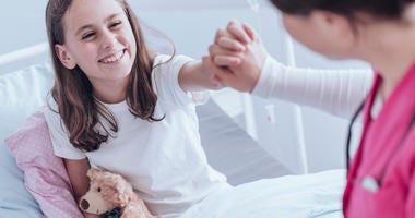 Nurse holding smiling girls hand in hospital bed