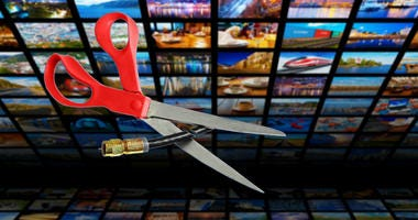 Image shows scissors cutting through a coaxial cable in front of a bank of tv screens