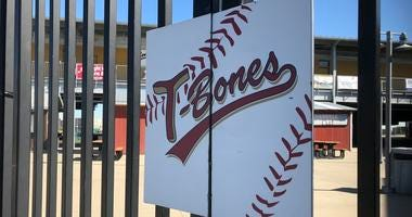 "A sign reading ""T-Bones"" hangs on the gate of the baseball stadium"