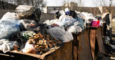 piles of trash in dumpsters