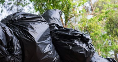stacks of filled black trash bags