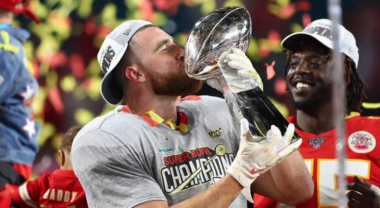 Kansas City Chiefs tight end Travis Kelce (87) kisses the Lombardi Trophy as he celebrates after defeating the San Francisco 49ers in Super Bowl LIV at Hard Rock Stadium