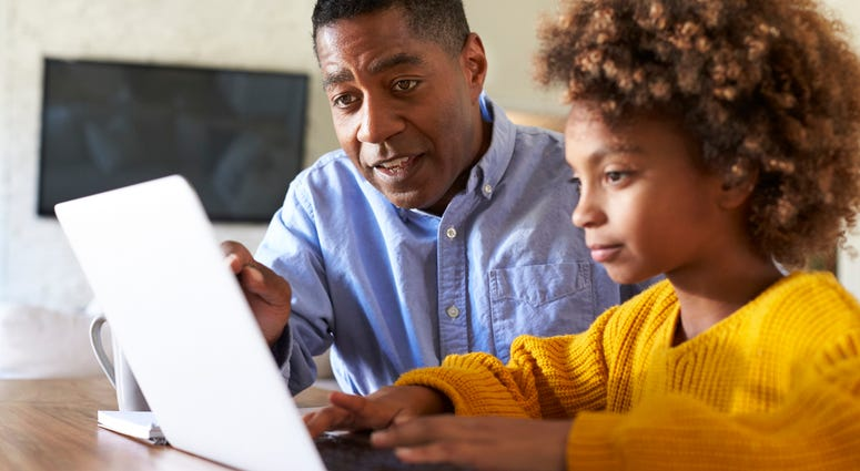 A tutor instructs a child at a computer.