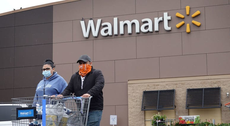 Shoppers wearing face coverings leaving a Walmart store.