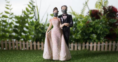 A wedding cake topper of bride and groom wearing face masks