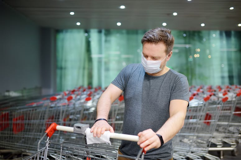 Man in face mask disinfects grocery shopping cart