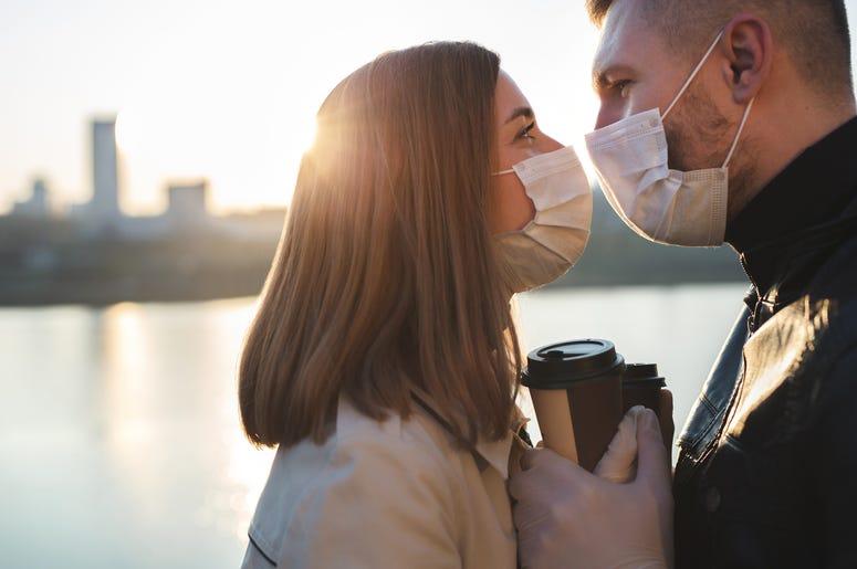 Couple wearing masks kissing near lake