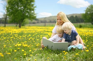Mother Reading Story Book to Two Young Children Outside in Meadow