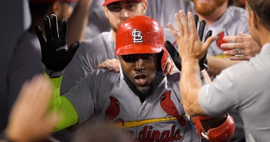 St. Louis Cardinals' Marcell Ozuna is congratulated by teammates in the dugout after hitting a two-run home run during the seventh inning of a baseball game against the Los Angeles Dodgers, Tuesday, Aug. 21, 2018, in Los Angeles.