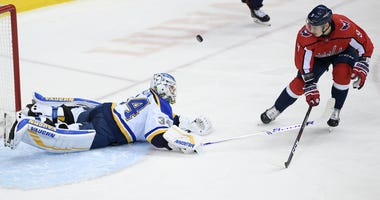 Washington Capitals defenseman Dmitry Orlov (9), of Russia, and St. Louis Blues goaltender Jake Allen (34) fight for the puck