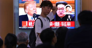 People watch a TV screen showing file footage of U.S. President Donald Trump, left, and North Korean leader Kim Jong Un during a news program at the Seoul Railway Station in Seoul, South Korea, Thursday, May 24, 2018.