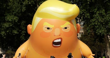 A six-meter high cartoon baby blimp of U.S. President Donald Trump is flown as a protest against his visit, in Parliament Square in London, England, Friday, July 13, 2018.