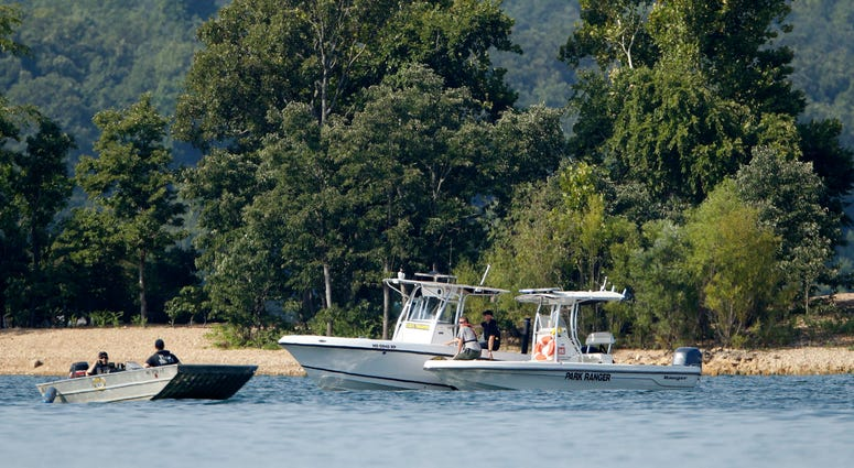 Emergency workers patrol an area Friday, July 20, 2018, near where a duck boat capsized the night before resulting in at least 13 deaths on Table Rock Lake in Branson, Mo.