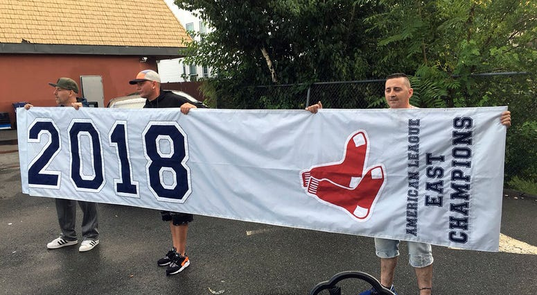 friends hold a banner they found in Somerville, Mass., that proclaims the Boston Red Sox are the 2018 American League East Champions