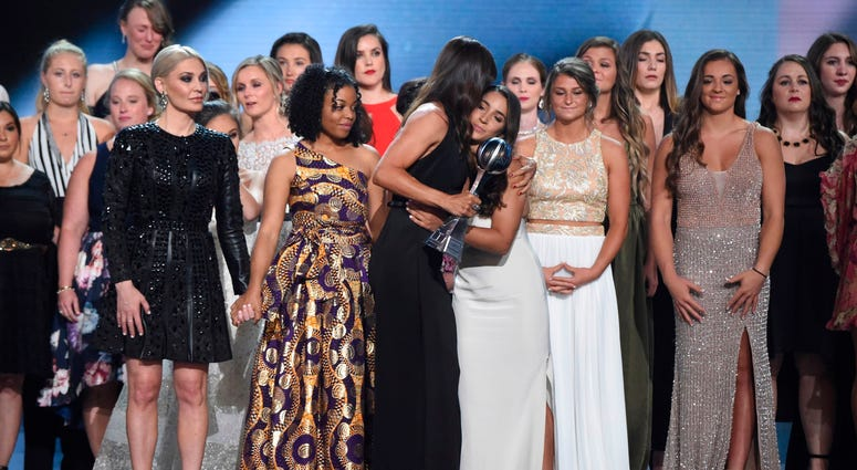 Jennifer Garner, front, embraces gymnast Aly Raisman after presenting the Arthur Ashe Award for Courage, at the ESPY Awards