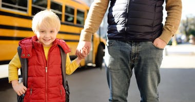 kid with father in front of school bus