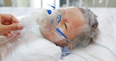 Toddler boy using nebulizer to cure asthma or pneumonia disease . Sick baby boy rest on patients bed and has inhalation therapy by the mask of inhaler. Respiratory Syncytial Virus