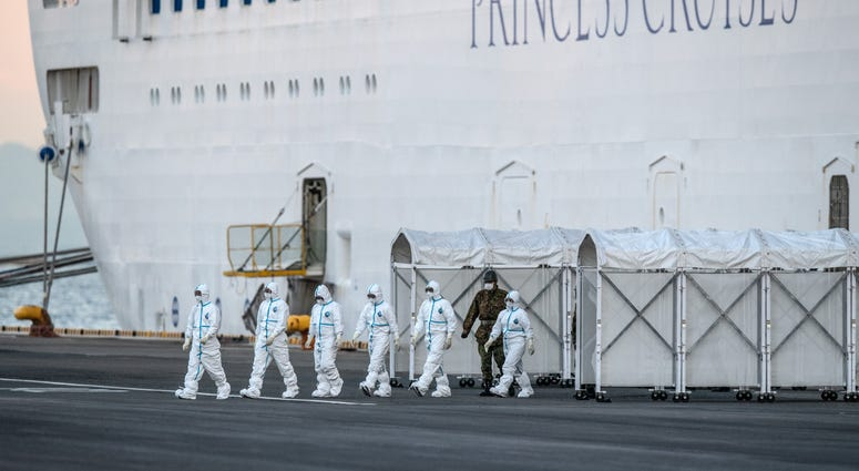 Emergency workers in protective clothing exit the Diamond Princess cruise ship at Daikoku Pier where it is being resupplied and newly diagnosed coronavirus cases taken for treatment as it remains in quarantine