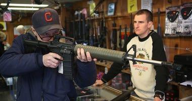 man looking through rifle before purchasing gun