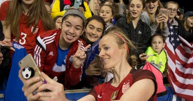 Becky Sauerbrunn poses for a photo with fans.