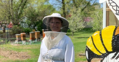Julie McKinney prepares to inspect her hives