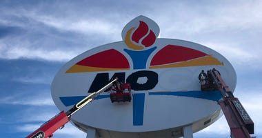 Workers repaint the landmark Amoco sign near Forest Park