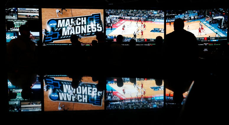 In this March 15, 2018 photo, people watch coverage of the first round of the NCAA college basketball tournament.