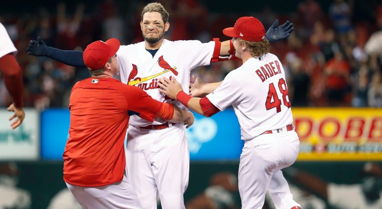 Yadier Molina  is congratulated by teammates Jedd Gyorko, left, and Harrison Bader after hitting a walk-off single