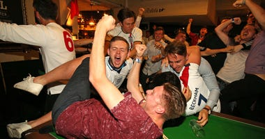 England supporters celebrate Harry Kane's winning goal at the Lord Raglan Pub in London