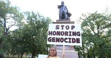 Kathy Dickerson holds a sign in front of the Christopher Columbus statue in Tower Grove Park in St. Louis on October 8, 2018.