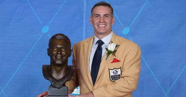 Quarterback Kurt Warner poses with his bust during the Professional Football HOF enshrinement ceremonies