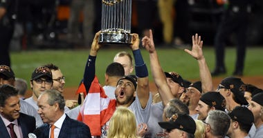 Houston Astros shortstop Carlos Correa (1) celebrates with the Commissioner's Trophy after the Houston Astros