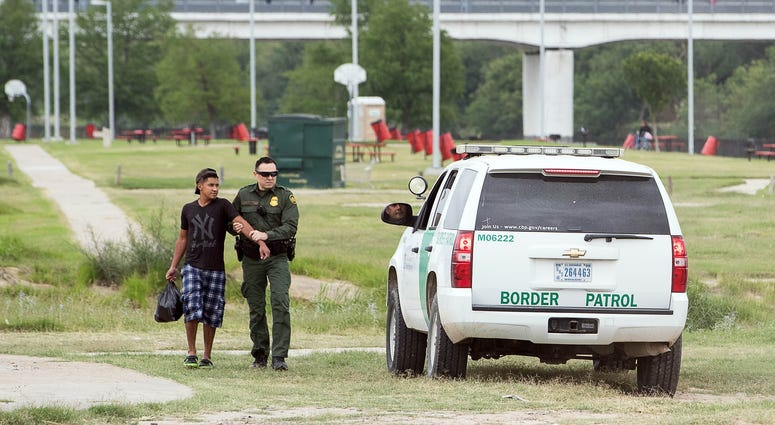 April 9, 2018; Laredo, TX, USA; A United States Border Patrol agent catches a man along the banks of the Rio Grande after watching him illegally cross the river from Mexico into the United States in Laredo, Texas.