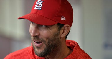 St. Louis Cardinals starting pitcher Adam Wainwright smiles in dugout.