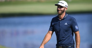 Dustin Johnson walks the green after hitting an eagle from 171 yards on the 18th hole