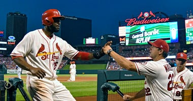 Dexter Fowler of the St. Louis Cardinals is congratulated in the dugout by manager Mike Matheny.