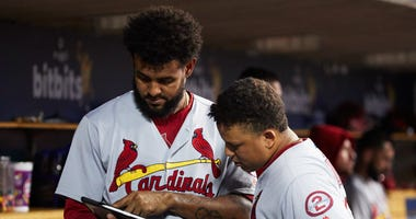 St. Louis Cardinals designated hitter Jose Martinez (38) and shortstop Yairo Munoz (34) look at an iPad