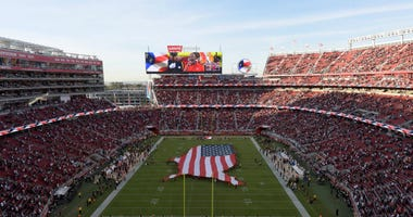 An American flag covers half the field during the national anthem