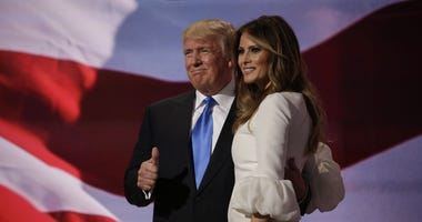 ul 18, 2016; Cleveland, OH, USA; Donald Trump gives a thumbs up to the crowd as he holds his wife Melania Trump after her speech during the 2016 Republican National Convention at Quicken Loans Arena.