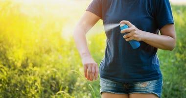 woman applying bug spray