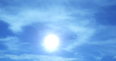 The burning-hot sun on background of blue sky and clouds