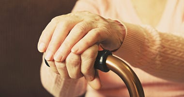 Elderly woman in nursing home, wrinkled hand with clearly visible veins holding walking quad cane