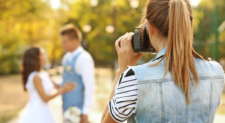 Young women taking photo of happy wedding couple in park