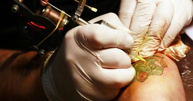 A tattoo artist applying his craft onto the hand of a female