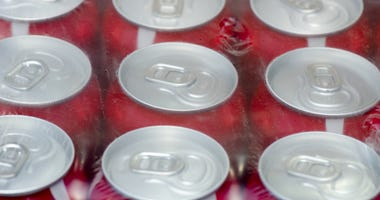 Red soda cans wrapped in a plastic foil