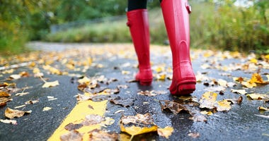 Autumn fall concept with colorful leaves and rain boots outside. Close up of woman feet walking in red boots.