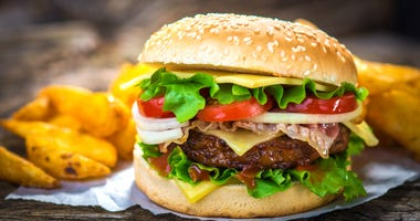 Homemade burger on wooden background.
