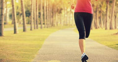 Runner athlete running at tropical park. woman fitness sunrise jogging workout wellness concept